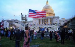 Protester proudly displays the American flag as the Capitol is infiltrated.