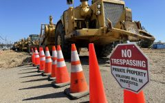 Heavy machinery sits parked behind construction cones and trespassing warnings