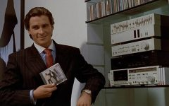 Christian Bale, portraying homicidal investment banker Patrick Bateman, grins while holding a CD (image courtesy of Lions Gate Films.)
